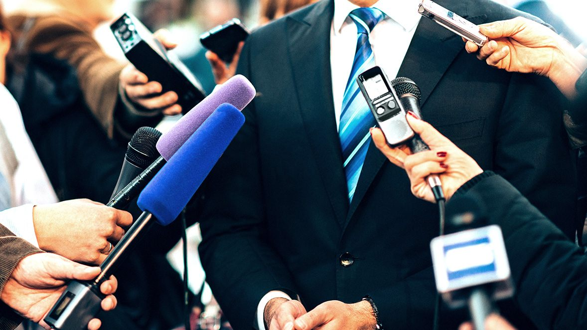 close up of businessman surrounded by microphones